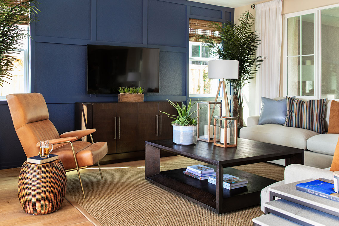 living room furniture set with tan suede chair, white chair with blue and orange pillows and blue painted accent wall