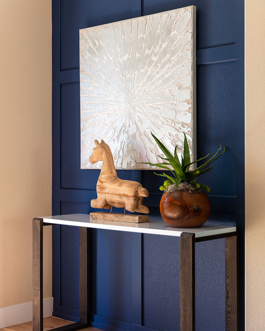 console table with wooden giraffe figurine and hanging picture on blue painted wall